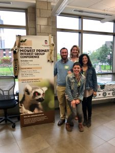 Members of the Strier Lab standing by a sign for the Midwestern Primate Interest Group Conference.